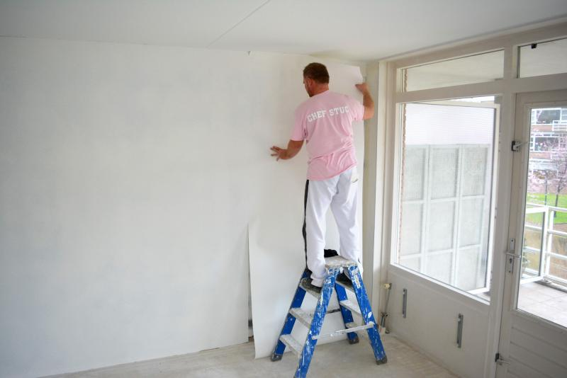 Schilder plaatst renovliesbehang
