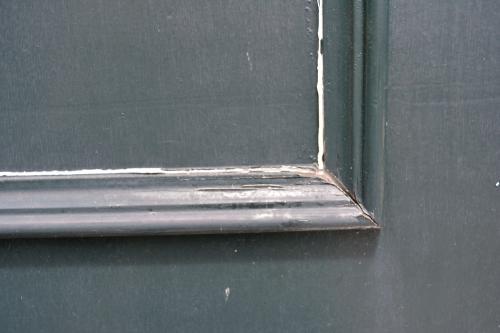 Closeup buitendeur. Afgebladderde verf repareren